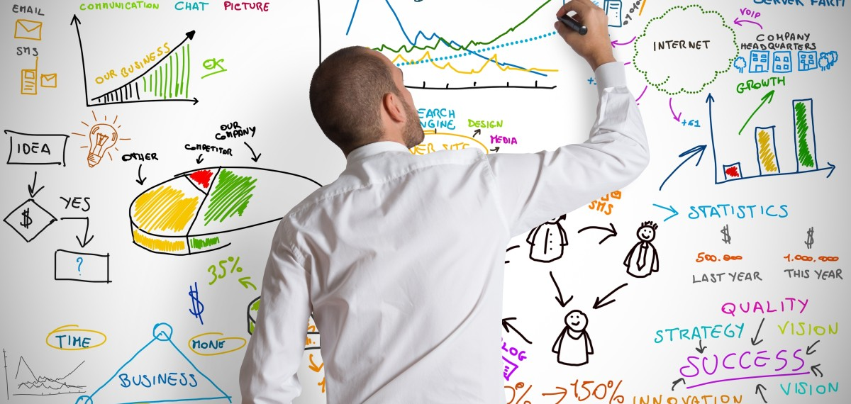 Young man in white shirt drawing digital marketing strategy ideas on a whiteboard