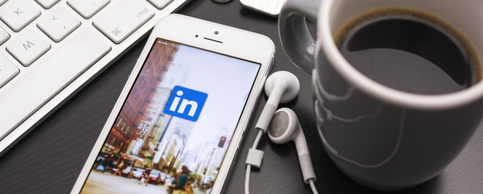LinkedIn icon on a mobile device on a coffee table